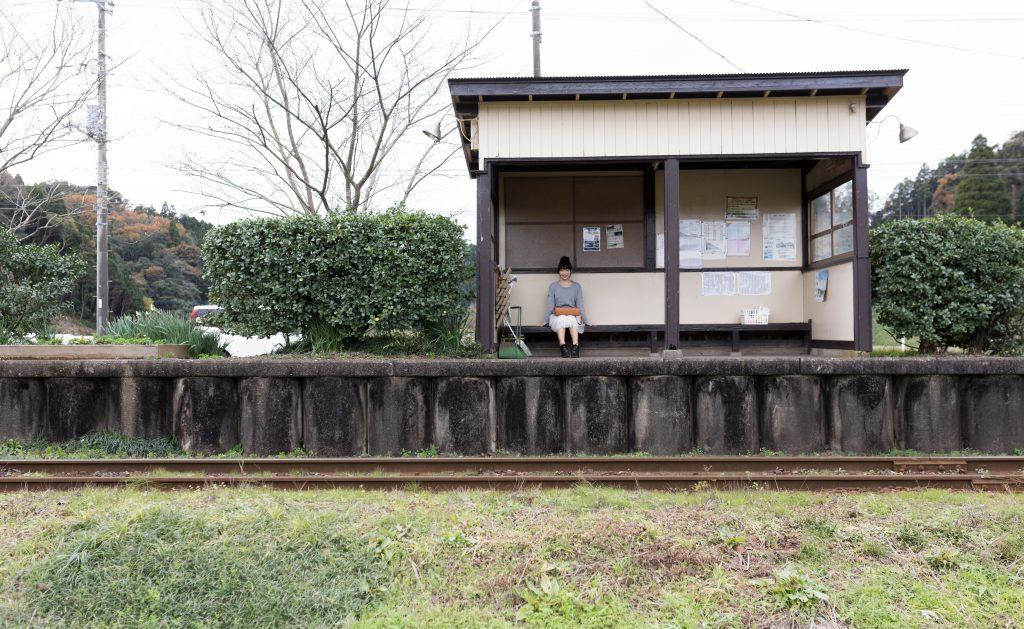 田舎のブラック企業に通う女性が、無人駅でたまにしか来ない電車を待つ姿